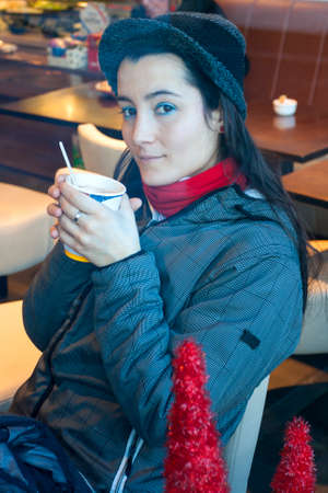 Close-up Young woman in a coffee shop drinking photo