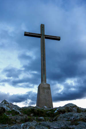 Christian cross silhouette on the top of the mountain. Bray, Ireland. photo