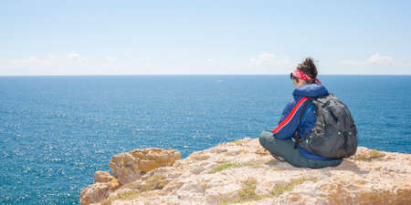 Woman sitting on the cliff in front of the sea photo