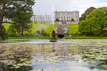 voted: Enniskerry, Ireland - May 11, 2014: Fountain of the Triton Lake in the Italian Garden at Powerscourt State. Powerscourt State was voted the third garden in the World by National Geographic in Sniskerry, Ireland on May 11, 2014 Editorial