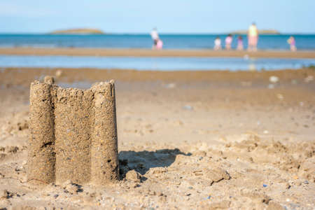 sandcastles: Sad castle on the beach with family playing at background
