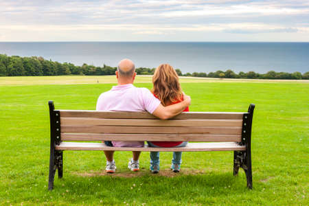 back seat: Rear view of middle age couple sitting on a bench looking at the sea Stock Photo
