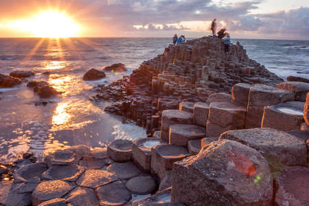 Mensen een bezoek aan Giant's Causeway bij de zonsondergang in Noord-Antrim, Noord-Ierland