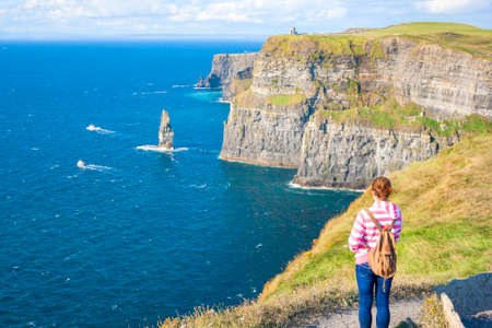 moher: Young woman at The Cliff of Moher, Co. Clare, Ireland Stock Photo