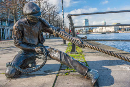 liffey: Dublin, Ireland - Oct 25, 2014: The Linesman statue at Liffey river in Dublin, Ireland on October 25, 2014