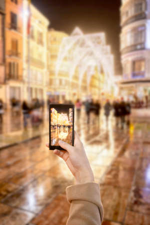 Smartphone taking a picture of christmas lights at Larios street in Malaga, Spain