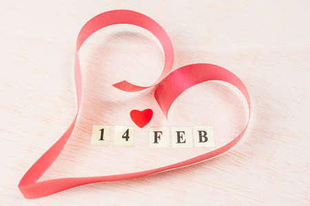 noteboard: 14 Feb, Valentines day on blonde wooden with a papper heart  background Stock Photo