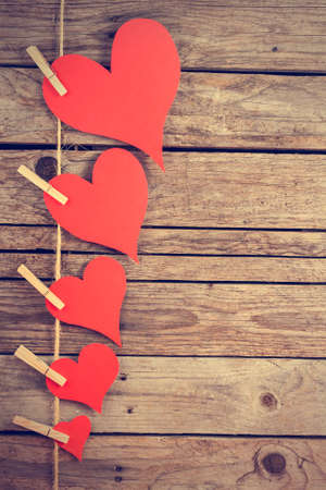 Five paper hearts hanging from a rope with wooden background