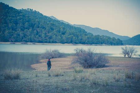 postproduction: Woman walking around a lake with vintage postproduction Stock Photo