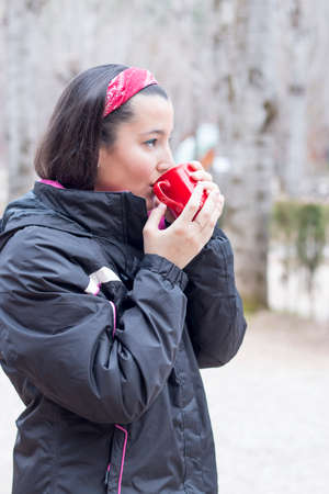 Beautiful woman holding a red mug with coffee wearing mountain cloth photo