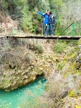 Young adult couple taking a selfie on the bridge over Borosa river in Cazorla, Jaen, Spain photo