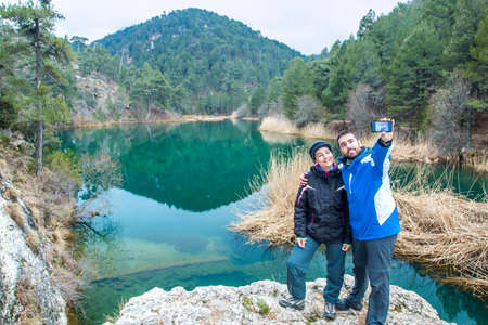 Young adult couple taking a selfie at the lake on Borosa river in Cazorla, Jaen, Spain photo