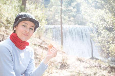 Beautiful young adult woman looking at camera and eating a croasant at the countryside photo