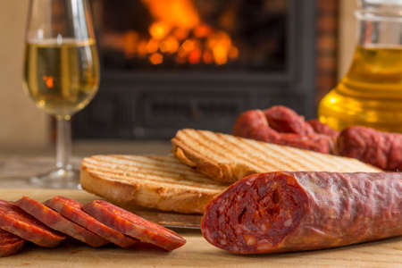 spanish tapa for brunch. Iberian chorizo, mature cheese, toasts, oil and white wine with fireplace at background