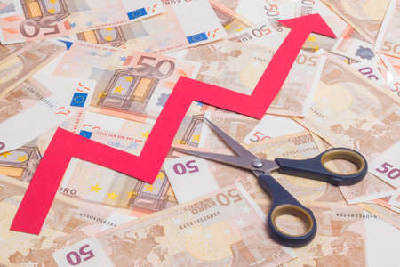 price cutting: Stop increasing euro value concept. Scissor cutting growing arrow over fifty euro notes background