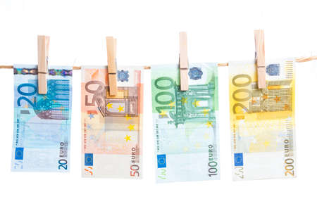 Euro banknotes hanging with peg from a rope isolated on white background
