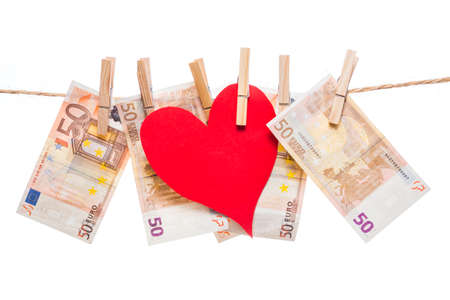 Price of love concept. Red paper heart hanging with fifty euro notes isolated on white background