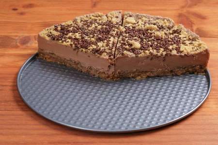 leftover: Closeup of half chocolate cheesecake on wooden table