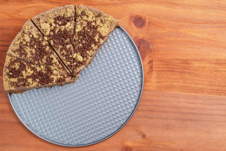 Closeup of half chocolate cheesecake on wooden table