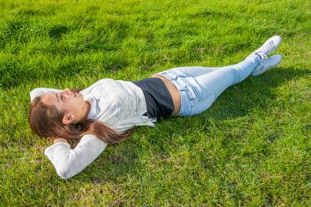 kilmainham: Beautiful teenager lying on the grass at the park Stock Photo
