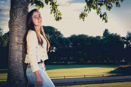 Closeup of beautiful casual teen leaning on a tree Stock Photo