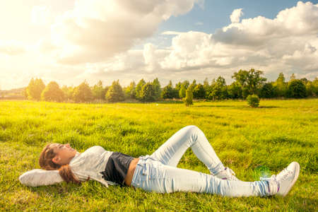 Beautiful teenager lying on the grass at the park Stock Photo