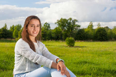 Beautiful teenager sitting on the grass at the park Stock Photo