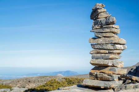 milepost: Stones pile at the mountain with blue sky at background