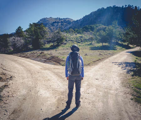 fork in the road: Hiker man choose between to directions at the mountain