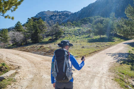 path ways: Hiker man choose between to directions at the mountain
