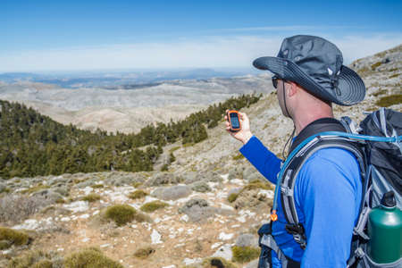 Hiker man using gps for positioning at the mountain