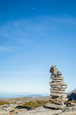 milepost: Stones pile at the mountain with the moon at blue sky