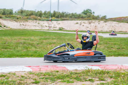 Man with arms up driving a kart. Winner in a karting race Stock Photo