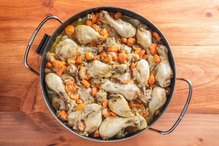 stew pan: Chicken with carrots stew in a big pan on wooden table