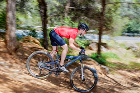 downhill: Young adult man riding a bike extreme downhill in nature Stock Photo