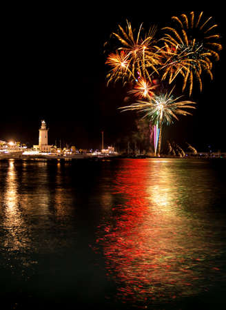 lighthouse at night: Fireworks over lighthouse on the Muelle uno in Malaga
