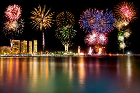 fuegos artificiales: Fuegos artificiales sobre el faro en el Muelle Uno de Málaga