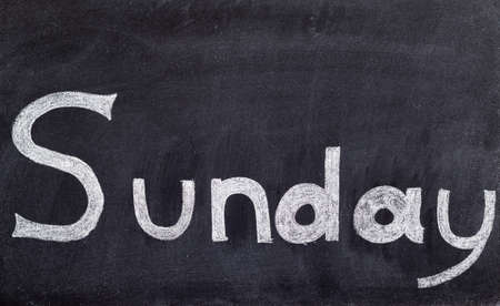 Sunday written on white on black chalkboard background Stock Photo