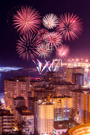 Aerial view of illuminated city in night and firework above it
