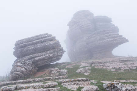 Gigantic rocks lying on hill slope in fog. Torcal in Antequera, Malaga