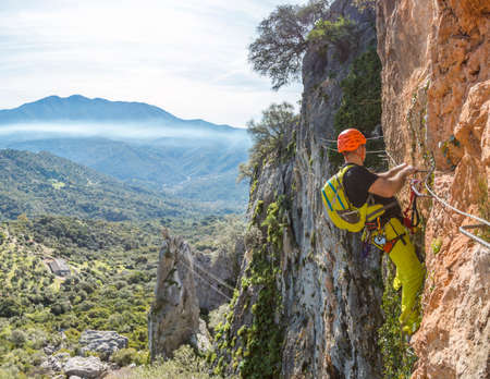 strong: Male climber in special outfit climbing cliff with mountaineering equipment