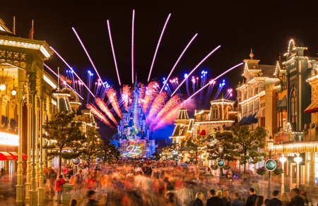 FRANCE, PARIS - Aug 17, 2017: View of colorful main street with Disney castle and bright fireworks bursting in night sky in Disneyland Paris, Marne-la-Vallee Chessy in Paris, France on August 17, 2017 新闻类图片