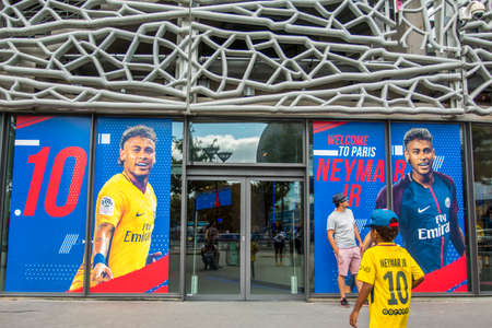 Paris, France - August 20, 2017: Doors of PSG Store with Poster of Neymar and little boy in his football player t-shirt in Paris, France on August 20, 2017