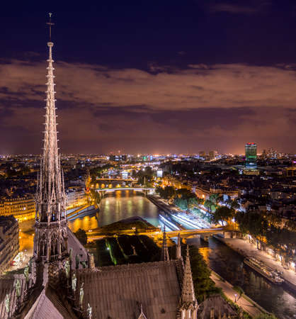 View of illuminated old city from viewpoint of old Gothic Notre-Dame cathedral with beautiful spire in Paris, France