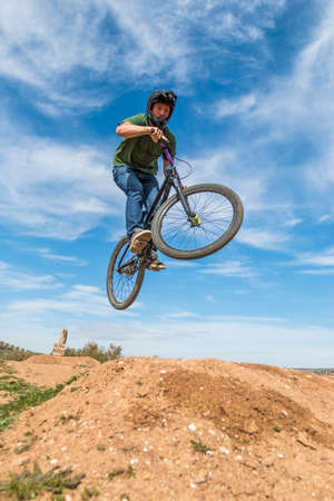 Confident sportsman flying on mountain bike on hills in nature Stock Photo