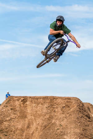 Front view of sportsman on mountain bike flying over hill in the nature Stock Photo