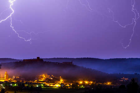 View of magnificent thunderstorm over small town at night Stock Photo