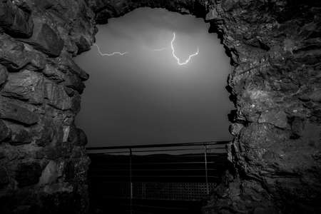 Beautiful view of majestic thunderstorm through old stone arch Stock Photo