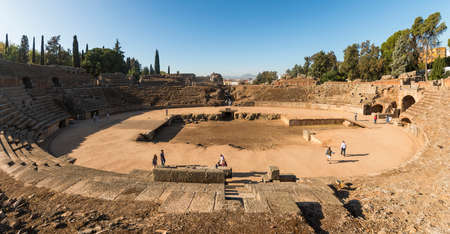 Merida, Spain - Oct 28, 2017: Unrecognizable tourists taking excursion on historic ruins of Roman Amphitheater in sunny day in Merida, Spain on October 28, 2017