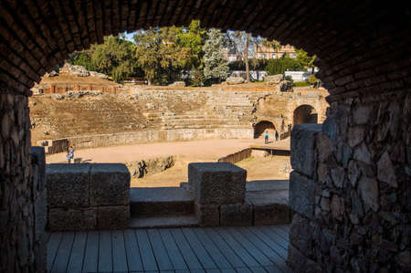 Merida, Spain - Oct 28, 2017: Arch and unrecognizable people walking on ruins of Roman Amphitheater of Merida in sunny day in Merida, Spain on October 28, 2017 新闻类图片